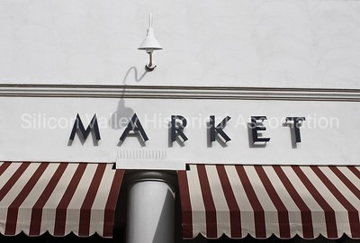 Market signage with red and white striped awning