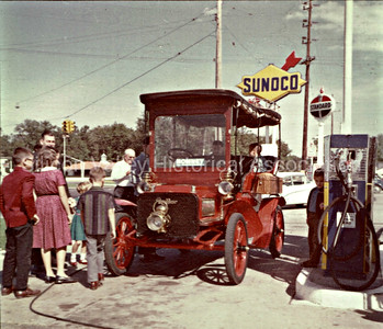 Vintage red car at a Sunoco station in Standish, Michigan in the early 1950s