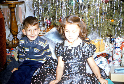Kids at Christmastime by Christmas tree, c. 1950s