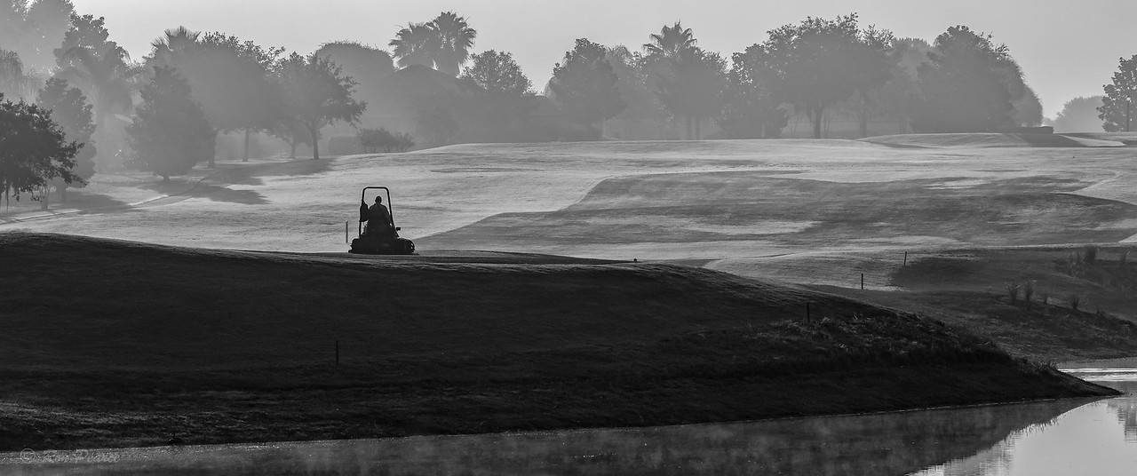 """Maintaining the Course""  In the early morning mist, the course is getting prepared for the  days golfers."
