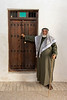 Man in thobe, keffiyeh and igal by an old doorway, Souk Al Arsah, Sharjah, UAE