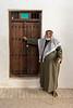 Man in thobe, keffiyeh and igal by an old doorway, Souk Al Arsah, Sharjah, UAE