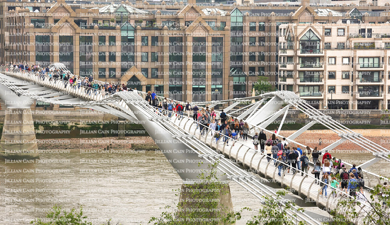 Aerial view of tourist crossing over the London Millennium Footbridge.  The bridge is nicknamed The Wobbly Bridge due to its unexpected swaying motion.