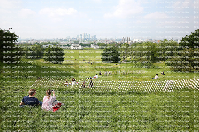 Tourists enjoying the view of London from the hill top at the Royal Observatory, location of the Prime Meridian.