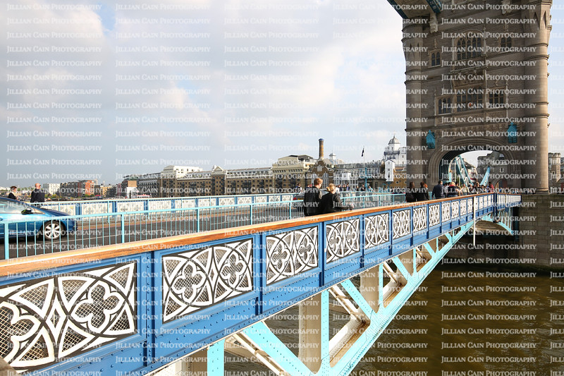 Tourist and cars cross over the River Thames by using the iconic blue and white Tower Bridge.
