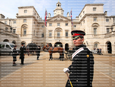 A Queen's Horse Guard stands on duty at the entrance of the Horse Guards building as the horse drawn carriages and motorbikes are readied for an official event.