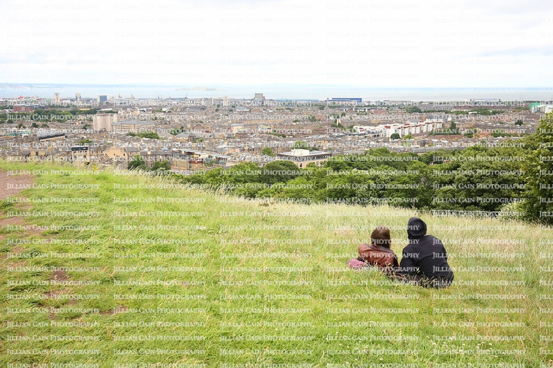 Couple enjoying Calton Hill's view overlooking beautiful Edinburgh, Scotland.