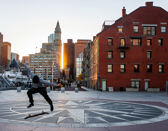 Skateboarding on the harborwalk during sunset in Boston