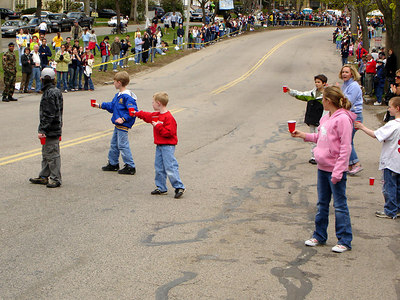 Little kids trying to hand water to the elite runners at the Boston Marathon - Chestnut Hill, MA ... April 17, 2006 ... Photo by Rob Page III