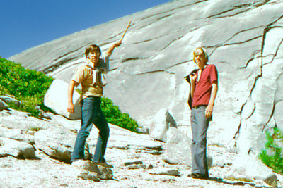 Yosemite - Looking at summit cap of Halfdome just before climbing it.  Rich pointing with stick that he picked up on this trip and now (Dec 2002) resides on a shelf in the den of Bob Page Jr.  Kevin Page beside him. by Robert W Page Jr - Aug 1973