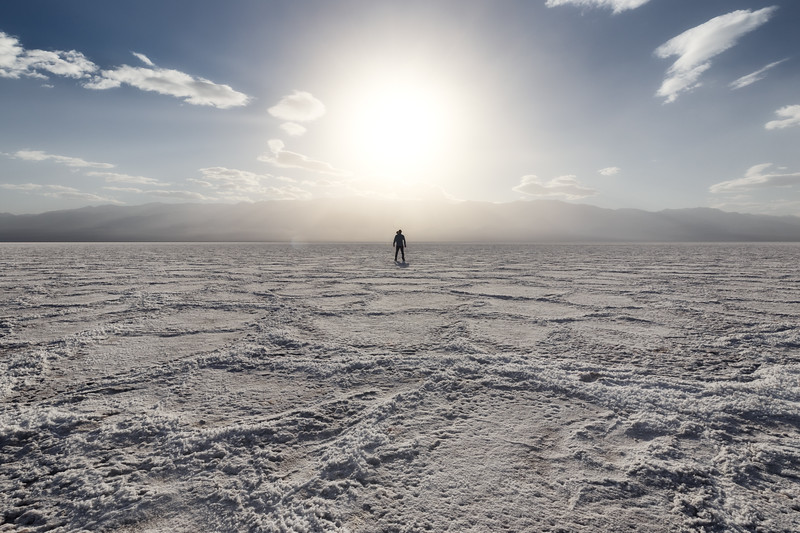 Death Valley, Badwater - Man in middle of tiles in front of setting sun like explosion