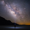 Death Valley, Badwater - Man alone on playa with headlamp observing Milky Way
