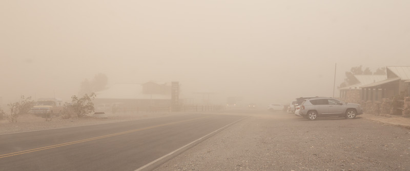 Death Valley, Stovepipe - Town in heavy sandstorm with parked cars, road, and buildings