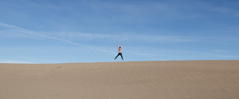 Death Valley, Mesquite Flat - Man jumping in air on top of a dune