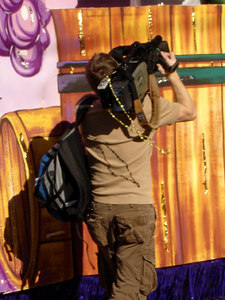 Even the camera man has beads.  Mardi Gras on Canal Street - New Orleans, LA ... February 26, 2006 ... Photo by Rob Page III