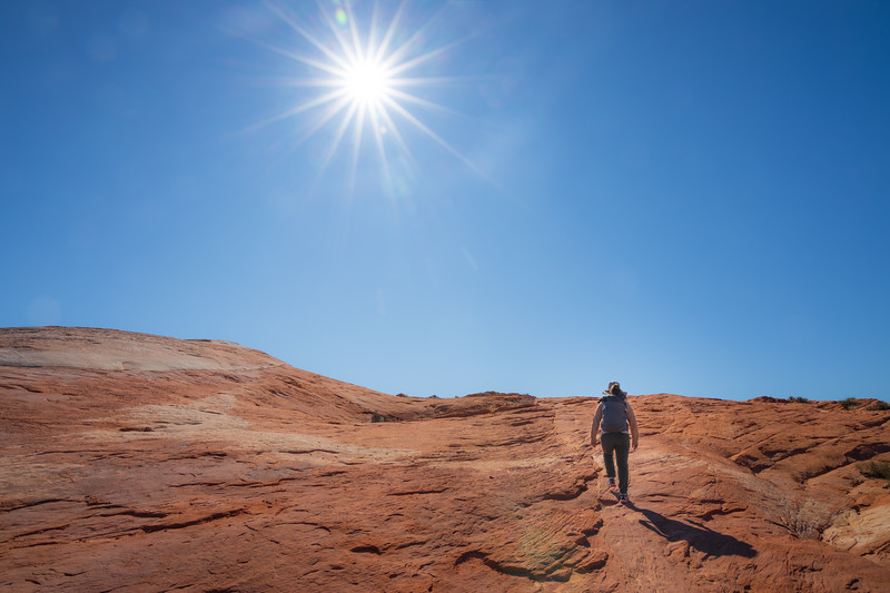 Valley of Fire, Fire Wave - Hiker ascending sandstone slopes under sun