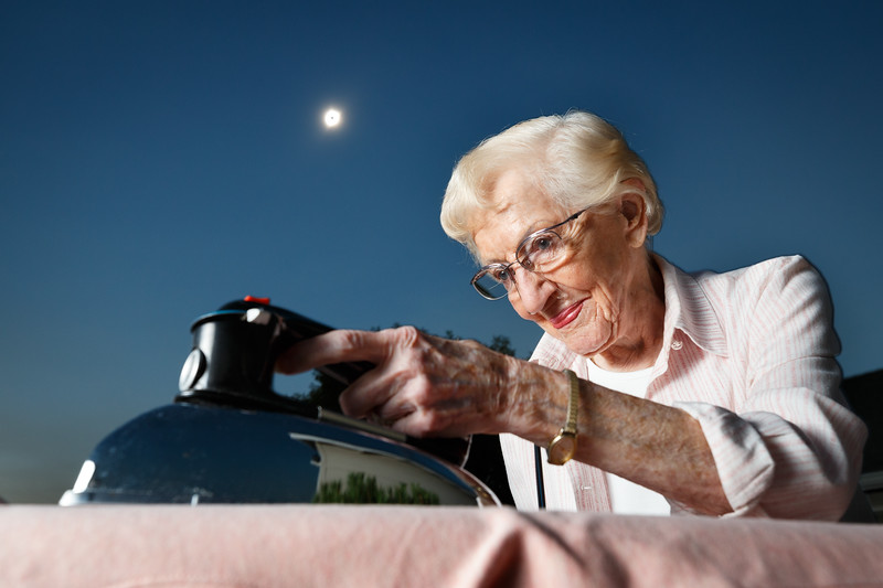 Oregon, Madras - old woman ironing her clothes during the total solar eclipse of August 21, 2017