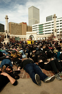 """In Civic Center park the demonstrators, dressed largely in black, prostrated themselves in a """"human oil spill."""""""