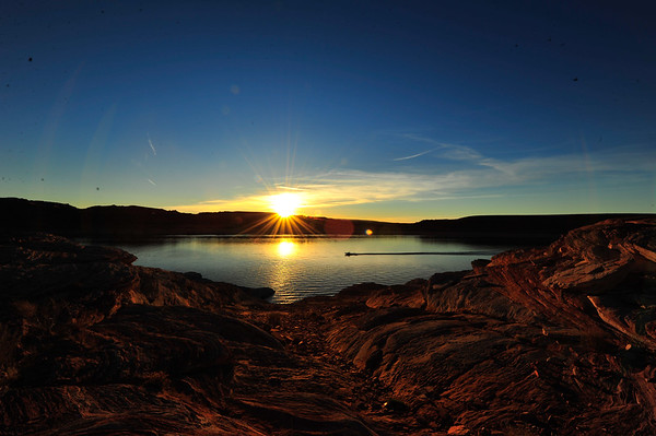 Sun on horizon with boat on Lake Powell