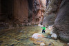 Zion, The Narrows - Woman hiker navigating river between tall canyon walls