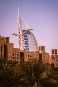 The Burj-Al_arab hotel in Dubai peaking from behind traditional looking old buildings from the UAE.