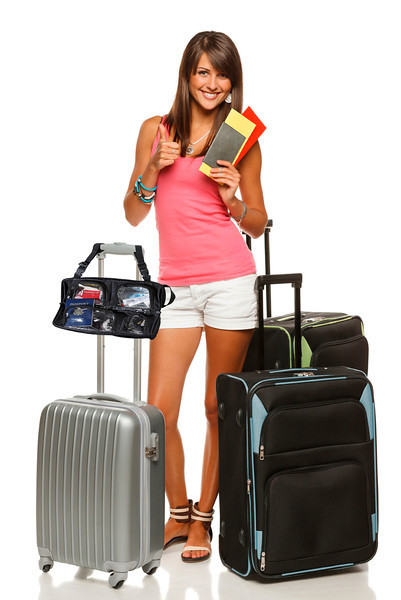 Full length of young female in casual standing with travel bags, holding passport and tickets, showing thumb up sign, isolated on white background