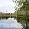 Peaceful setting of a flag flying at half staff is reflected in the pond below