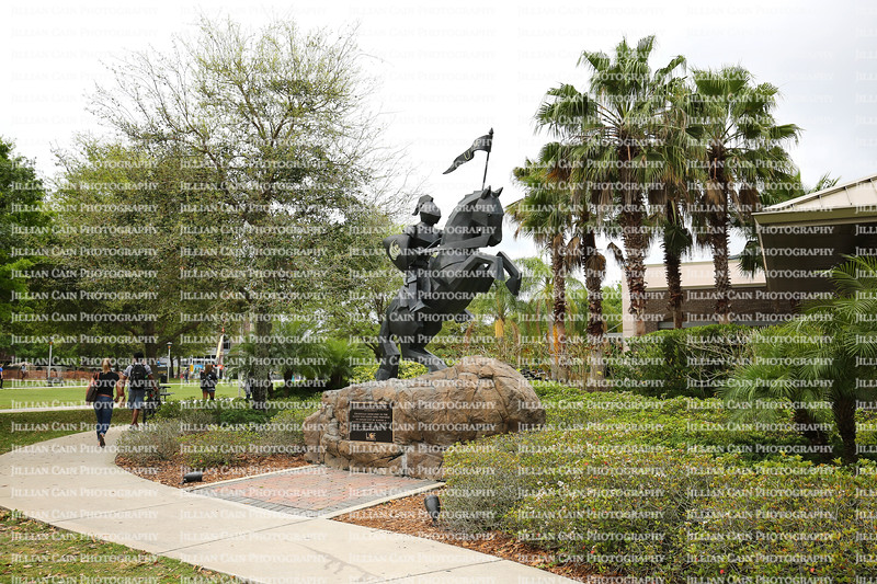Students walk past the University of Central Florida's Victory Knight statue, dedicated to the UCF Alumni and a popular graduation day photo spot.