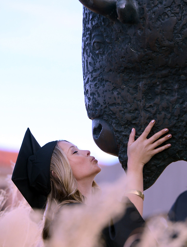 """CU grad, Caroline Cislo, gives the buffalo outside the Coors Events Center, a final kiss goodbye after the ceremony on Friday.<br /> The University of Colorado Boulder held its winter commencement ceremony on Friday, Dec. 21, in the Coors Events Center<br /> For more photos and a video of graduation, go to  <a href=""""http://www.dailycamera.com"""">http://www.dailycamera.com</a>.<br /> Cliff Grassmick  / December 21, 2012"""