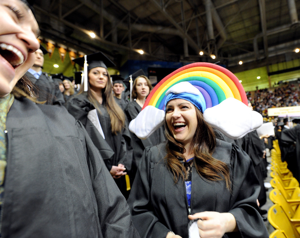 """Caitlin Duffy, left, loans Audrey Kettle her rainbow head dress on graduation day.<br /> The University of Colorado Boulder held its winter commencement ceremony on Friday, Dec. 21, in the Coors Events Center<br /> For more photos and a video of graduation, go to  <a href=""""http://www.dailycamera.com"""">http://www.dailycamera.com</a>.<br /> Cliff Grassmick  / December 21, 2012"""