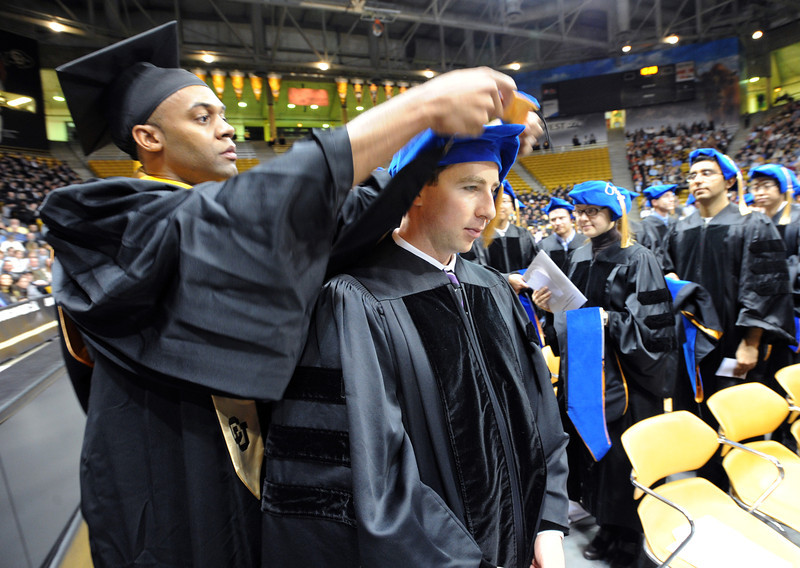 """Doctoral candidate, Michael Maslanik, gets hooded by Cory  Edwards.<br /> The University of Colorado Boulder held its winter commencement ceremony on Friday, Dec. 21, in the Coors Events Center<br /> For more photos and a video of graduation, go to  <a href=""""http://www.dailycamera.com"""">http://www.dailycamera.com</a>.<br /> Cliff Grassmick  / December 21, 2012"""