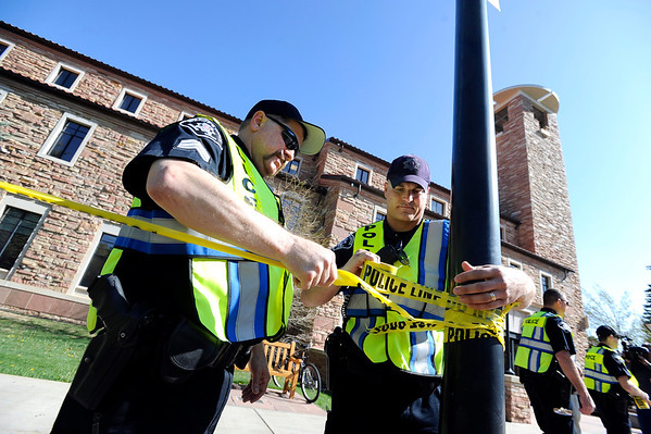 """Jefferson County Sheriff deputies Seth Poe, right,  and Paul Heger work to put up police tape to close off the Norlin Quad on the University of Colorado campus in Boulder on April 20, 2012. For more photos and video of 4/20 on the CU campus in Boulder go to  <a href=""""http://www.dailycamera.com"""">http://www.dailycamera.com</a><br /> Jeremy Papasso/ Camera"""
