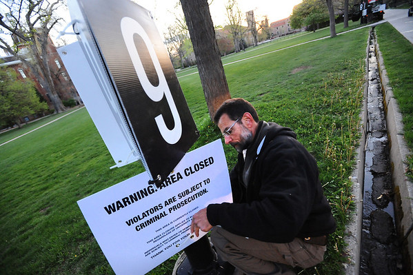 A man who asked that his name not be used places closure signs on the Norlin Quad of the University of Colorado Boulder Campus  Friday April 20, 2012. This was the first of several measures to keep the annual 4/20 pot smoking gathering off the campus. <br /> <br /> Photo by Paul Aiken   /  The Camera