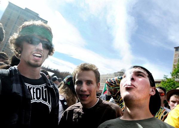 "An unidentified man, at right, exhales a plume of smoke after smoking a marijuana cigarette in the crowd of marijuana supporters outside of the Duane Physics building during the 4/20 rally on the University of Colorado campus in Boulder on Friday, April 20. For more photos and video go to  <a href=""http://www.dailycamera.com"">http://www.dailycamera.com</a><br /> Jeremy Papasso/ Camera"