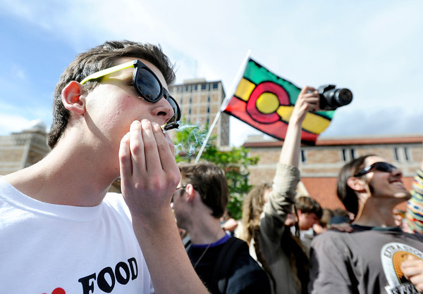 "Joe, last name not given, at left, smokes a marijuana cigarette in the crowd during the 4/20 rally on the University of Colorado campus in Boulder on Friday, April 20. For more photos and video go to  <a href=""http://www.dailycamera.com"">http://www.dailycamera.com</a><br /> Jeremy Papasso/ Camera"
