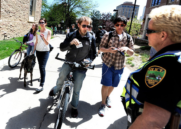 "University of Colorado junior Chris Yarrish, center, shows his student identification card to Colorado State University police officer Bozdech, right, at a checkpoint on the CU campus in Boulder on Friday, April 20. CU has closed its campus to the public, only allowing students or people with permits enter the premises in order to stop the 4/20 rally from happening. For more photos and video of the 4/20 event go to  <a href=""http://www.dailycamera.com"">http://www.dailycamera.com</a><br /> Jeremy Papasso/ Camera"