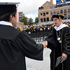 Graduate Austin Bisnow, left, shakes the hand of CU President, Bruce Benson, as Benson takes the stage.<br /> The University of Colorado conferred 5,825 degrees at Folsom Field Friday, May 7, 2010.<br /> Cliff Grassmick / May 7, 2010