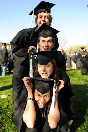 Garrett Hedman, top, David Azari, Klew Williams, and Aisha Thiessen, form a graduation totem for a friend's photo op.<br /> The University of Colorado conferred 5,825 degrees at Folsom Field Friday, May 7, 2010.<br /> Cliff Grassmick / May 7, 2010