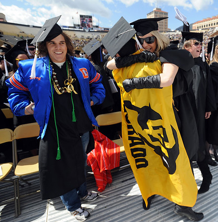 Chris Mulvany, left, in Bronco gear, hangs out while Dustin Farivar hugs Nicole Lyons as the Arts and Sciences grads are announced.<br /> The University of Colorado conferred 5,825 degrees at Folsom Field Friday, May 7, 2010.<br /> Cliff Grassmick / May 7, 2010