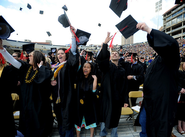 Kelly Schuberth, left, Haley Firtzen, Charissee Clark, Philip Thurner, and Adam Ladwig, all Journalism graduates, throw their caps in the air.<br /> The University of Colorado conferred 5,825 degrees at Folsom Field Friday, May 7, 2010.<br /> Cliff Grassmick / May 7, 2010