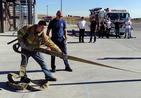 "CU student, Blake Padilla, pulls in a fire hose in full fire gear during a training exercise. Fireman Cameron Knapp is supervising.<br /> The Boulder Fire Department hosted the Leadership Fire Academy for University of Colorado students from sororities, fraternities, student government, and other organizations in hopes of giving them life-saving information they care share with their peers.<br /> For more photos and a video, go to  <a href=""http://www.dailycamera.com"">http://www.dailycamera.com</a><br /> Cliff Grassmick / September 25, 2010"
