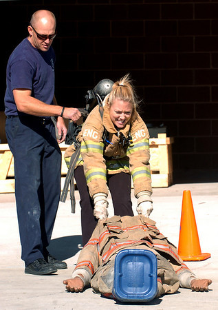 """CU student, Amy Johnson, pulls a 200-pound """"victim"""" as  Boulder fireman, Cameron Knapp,  encourages her.<br /> The Boulder Fire Department hosted the Leadership Fire Academy for University of Colorado students from sororities, fraternities, student government, and other organizations in hopes of giving them life-saving information they care share with their peers.<br /> For more photos and a video, go to  <a href=""""http://www.dailycamera.com"""">http://www.dailycamera.com</a><br /> Cliff Grassmick / September 25, 2010"""