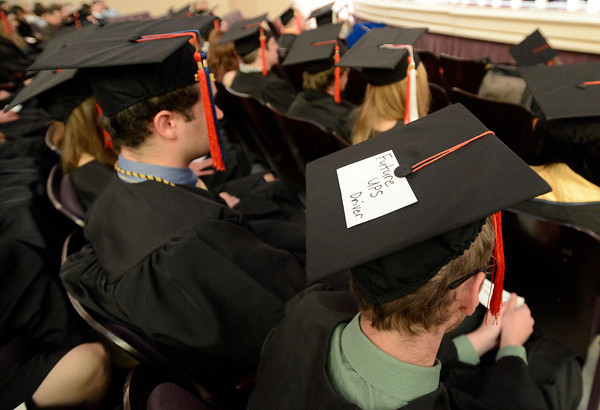 University of Colorado graduate Daniel Edwards sits with a funny sign on the top of his graduation cap during the Journalism and Mass Communication School graduation on Thursday, Dec. 20, at the Macky Auditorium.<br /> Jeremy Papasso/ Camera