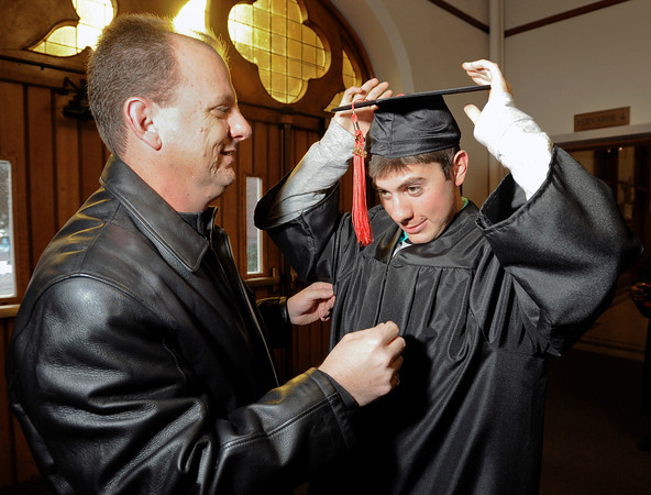 University of Colorado graduate D.J. Ursetta Jr. gets some help with his graduation cap from his father David Ursetta during the Journalism and Mass Communication School graduation on Thursday, Dec. 20, at the Macky Auditorium.<br /> Jeremy Papasso/ Camera