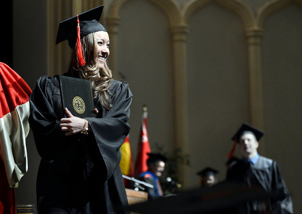University of Colorado graduate Katherine LaSalle smiles as she holds her diploma up to the crowd during the Journalism and Mass Communication School graduation on Thursday, Dec. 20, at the Macky Auditorium.<br /> Jeremy Papasso/ Camera