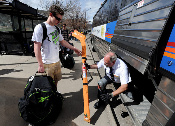 """Zachary Clawson, of Los Gatos, CA, is going back home with his hockey sticks. He gets help from Neal Newby of RTD at the Euclid and Broadway bus stop.<br /> University of Colorado students are leaving for Spring break. For more photos of students going back to Cali, go to  <a href=""""http://www.dailycamera.com"""">http://www.dailycamera.com</a>.<br /> Cliff Grassmick/ March 17, 2011"""