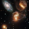 Stephan's Quintet<br /> Galactic Wreckage in Stephan's Quintet<br /> <br /> A clash among members of a famous galaxy quintet reveals an assortment of stars across a wide color range, from young, blue stars to aging, red stars.