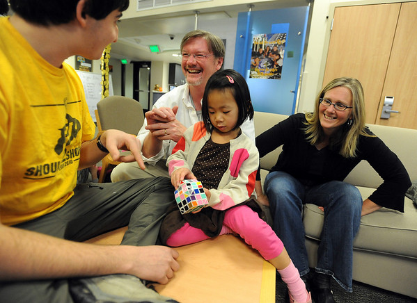 "CU student Eitan Cher, left, helps Thalia Douglass with a cube he designed, while parents Scot and Kathleen watch in the background.<br /> The Douglass family lives with CU students in Andrews Hall.<br /> For more photos, go to  <a href=""http://www.dailycamera.com"">http://www.dailycamera.com</a>.<br /> Cliff Grassmick / November 20, 2009"