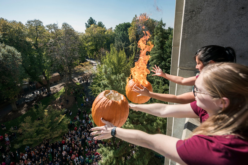 Elizabeth Pham (back) and Carissa Leveille (front) drop a flaming pumpkin with the Society of Physics Students and the Department of Physics at Chico State in a comedic and educational experiment to test how and why things fall drop plenty of falling pumpkins from Butte Hall during the 30th Annual Pumpkin Drop on Tuesday, October 31, 2017 in Chico, Calif.<br /> (Jason Halley/University Photographer)