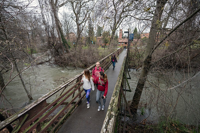 Students walk across one of the bridges over Big Chico Creek that runs full of water after recent wet weather on Wednesday, February 8, 2017 in Chico, Calif.  (Jason Halley/University Photographer)